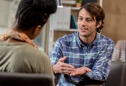 Frau spricht mit männlichem Psychotherapeut – Master Beratungspsychologie studieren
