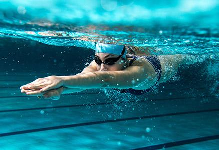 Schwimmerin unter Wasser im Hallenbad – Master Sportwissenschaft studieren