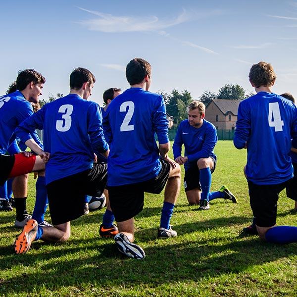 Fußballspieler beim Dehnen, Kinder- & Jugendtraining Bachelorstudium