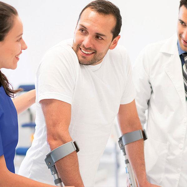 Mann auf Krücken mit Arzt und Therapeutin, Prävention Regeneration & Rehabilitation studieren