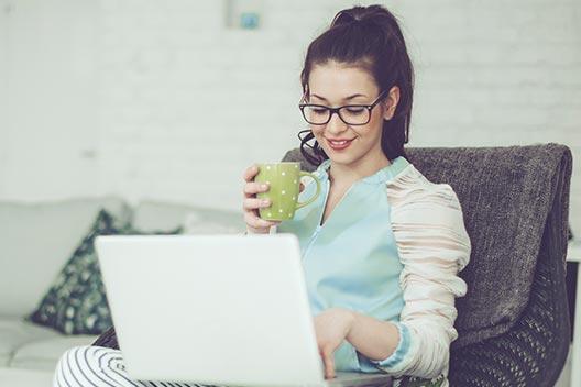 Studieninteressierte sitzt vor dem Laptop und fordert Informationen zum Studium an.