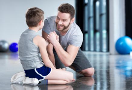 Mann unterhält sich mit Kind in Sporthalle – Soziale Arbeit & Sport studieren