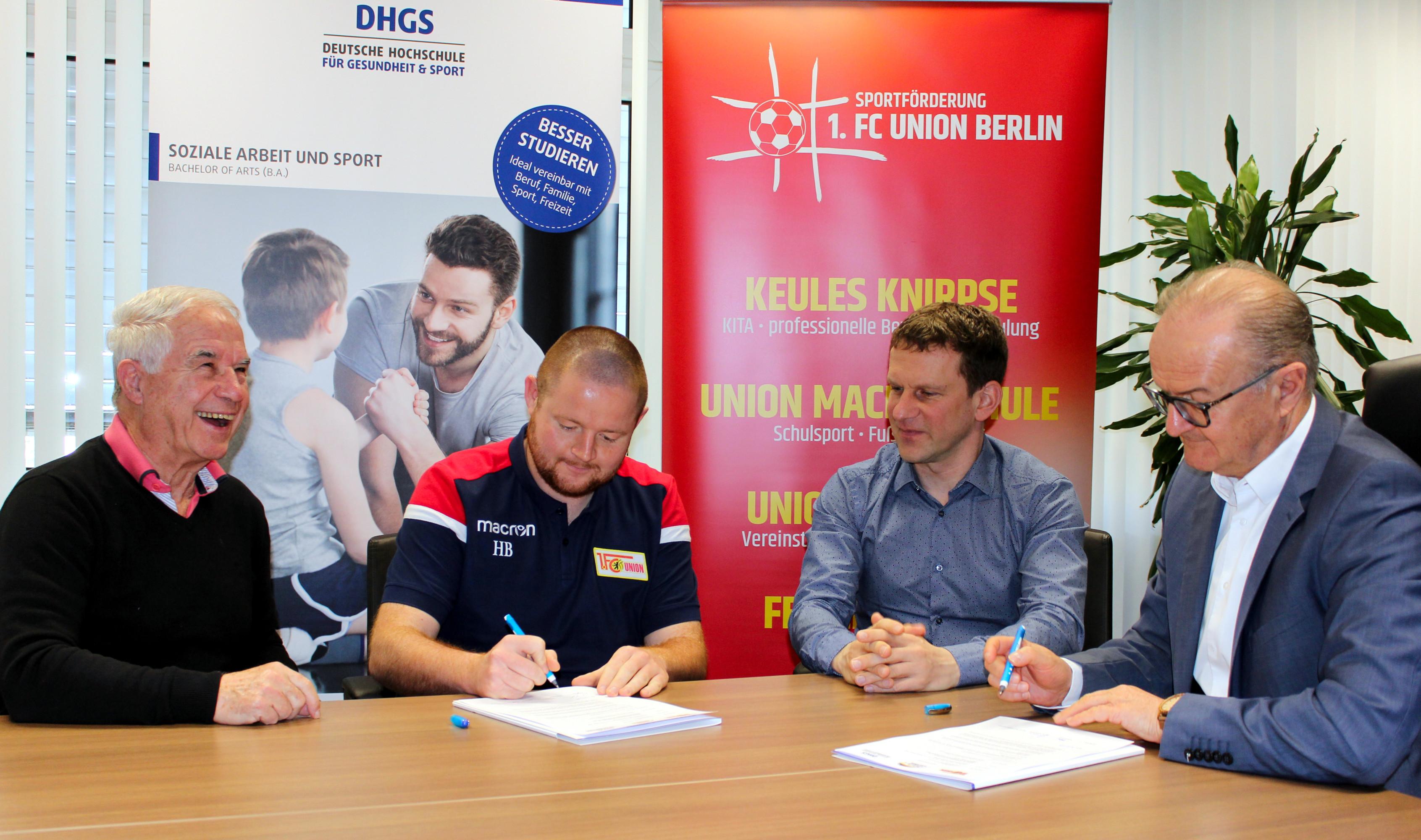 Vier männliche Personen unterzeichnen einen Kooperationsvertrag zwischen der DHGS Hochschule und dem 1.FC Union Berlin