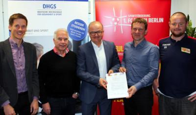 Fünf männliche Personen mit einem Kooperationsvertrag zwichen der DHGS Hochschule und dem 1.FC Union Berlin