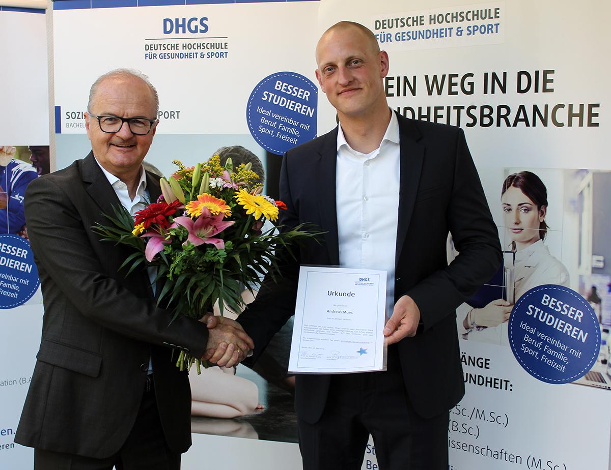 Präsident Binninger überreicht Kanzler Mues Jubiläumsurkunde und Blumenstrauß