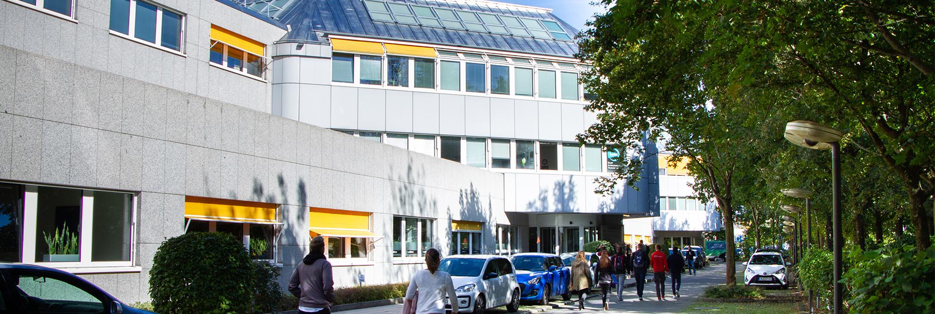 Studenten gehen zum Eingang des Ismaninger Standortes.