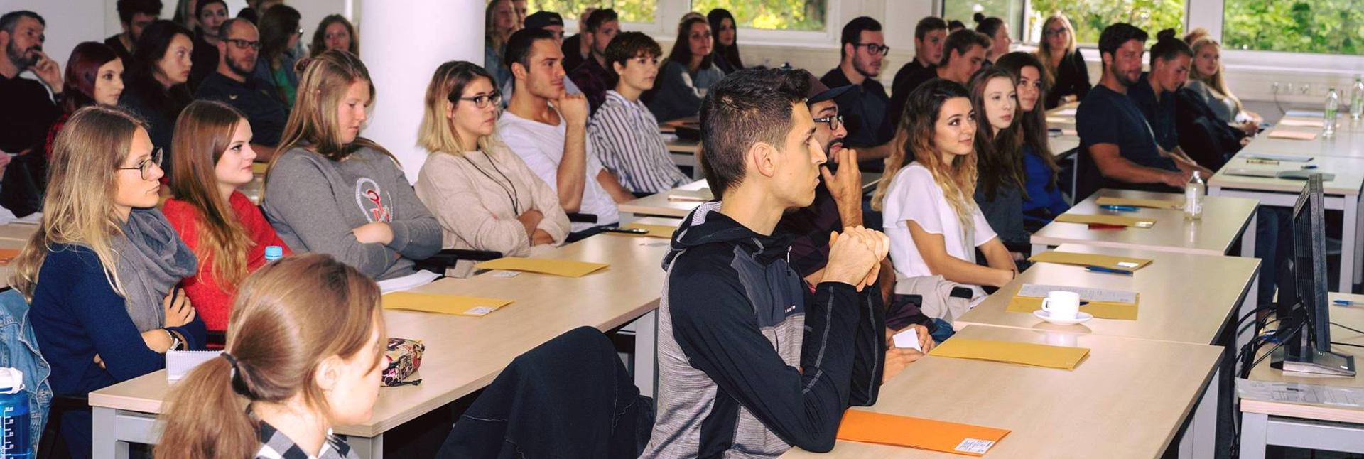 Studenten blicken interessiert nach vorne zum Dozenten.
