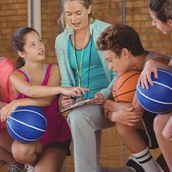 Eine Bewegungspädagogin bespricht mit den Trainingsablauf mit einigen Kindern.