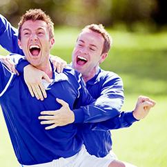 Fußballer umarmen sich stürmisch und feiern ein gerade gefallenes Tor.