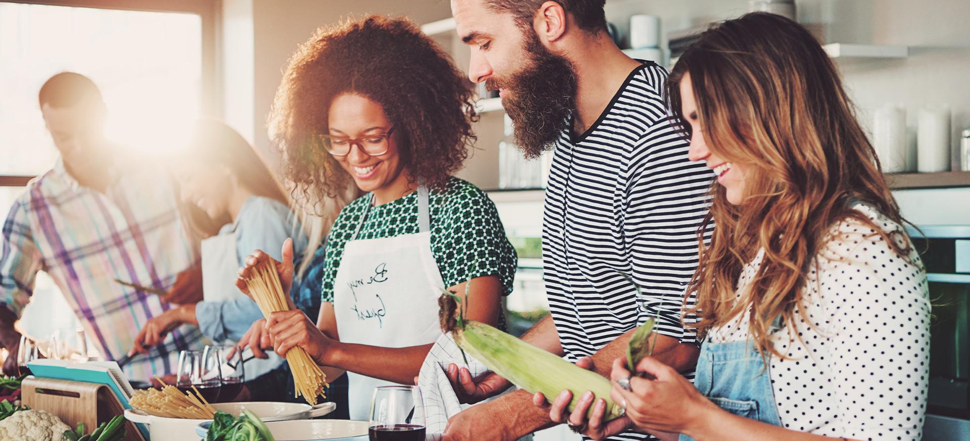 Eine Ernährungsberaterin kocht gemeinsam mit einer Gruppe Menschen.
