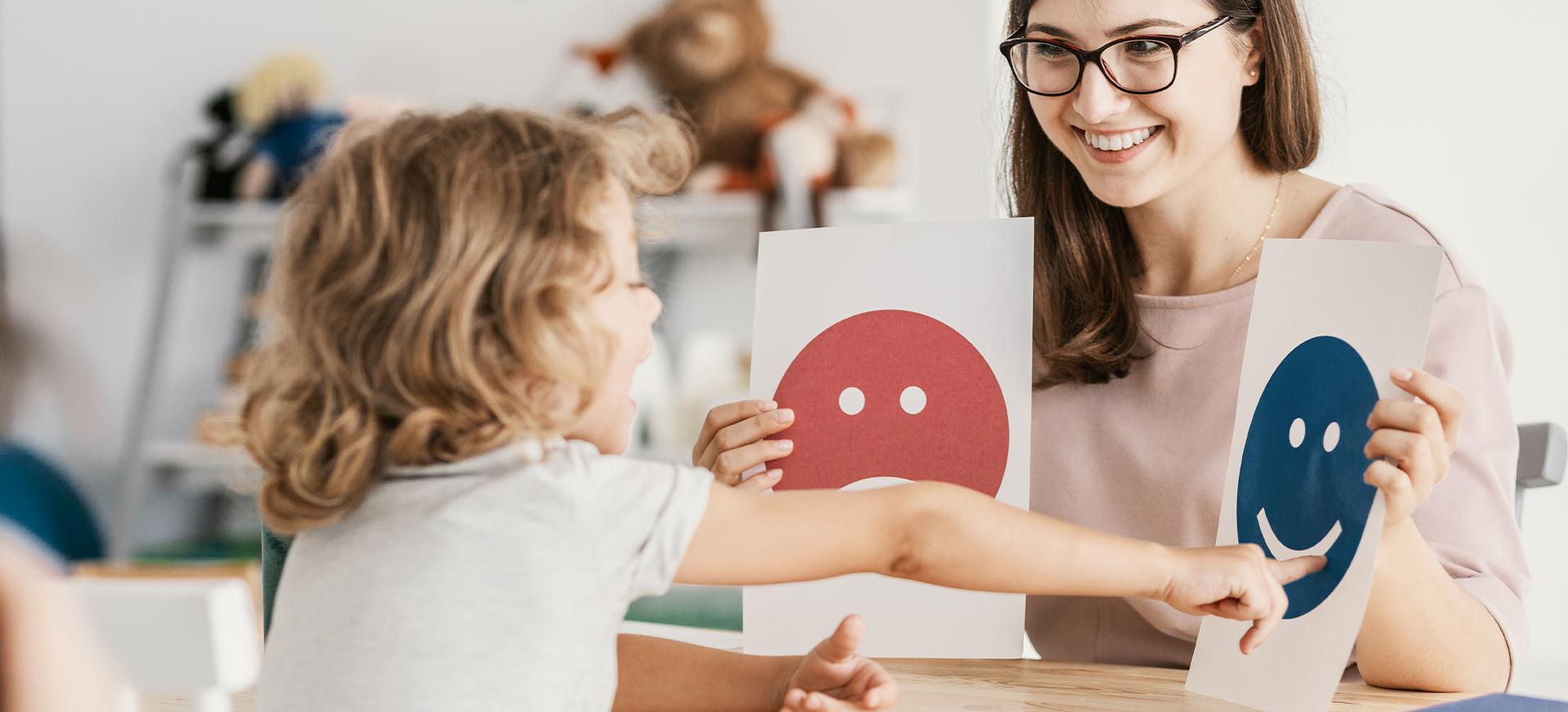 Eine Kinder- & Jugendpsychologin spielt ein Spiel mit einem kleinen Jungen.