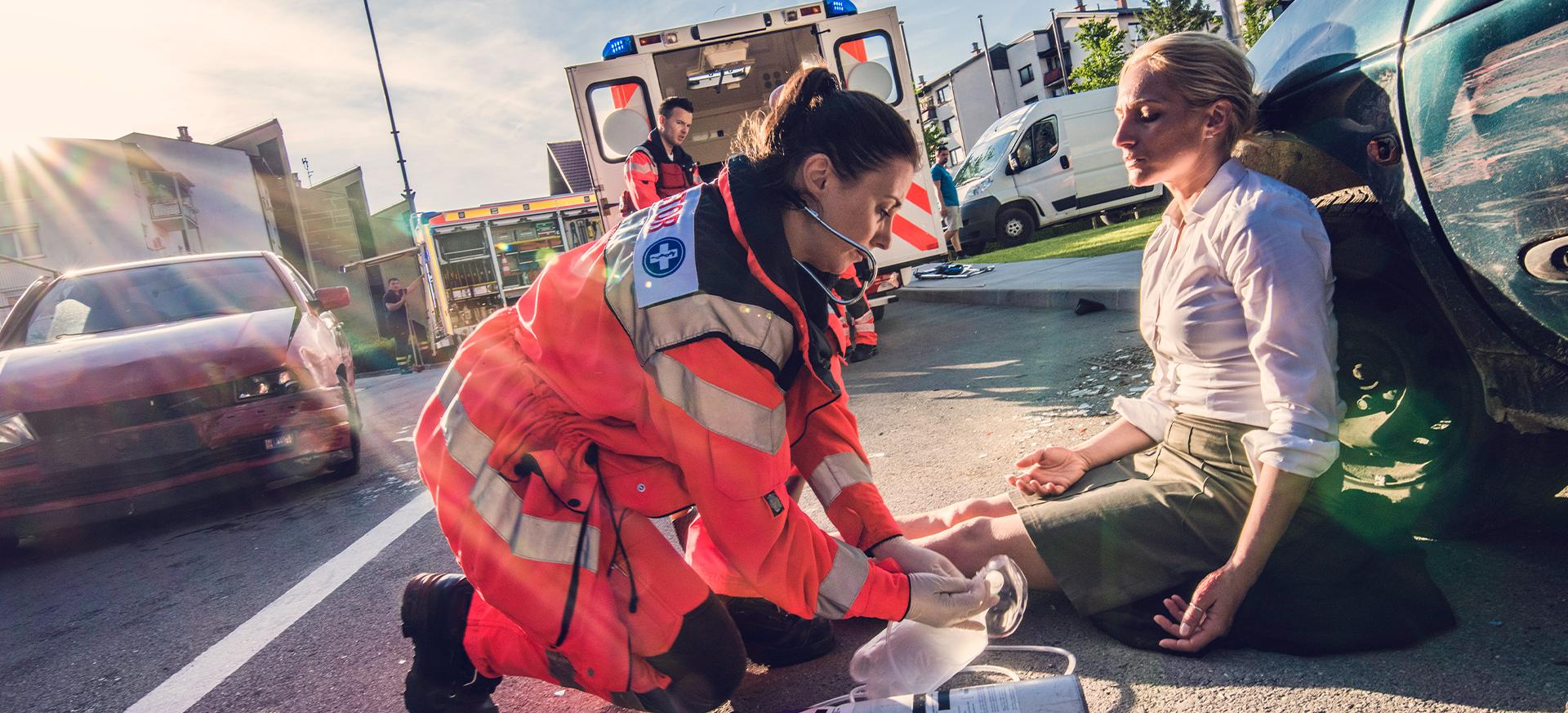 Retttungsdienstmitarbeiterin leistet Erste Hilfe bei einem Unfallopfer.