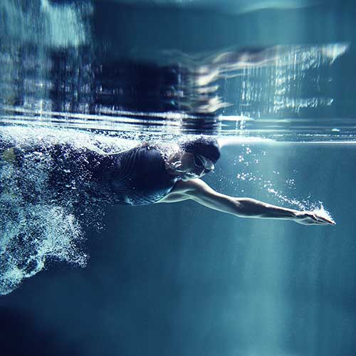 Eine Schwimmerin durchbricht das Wasser mit kraftvollen Schwimmzügen.