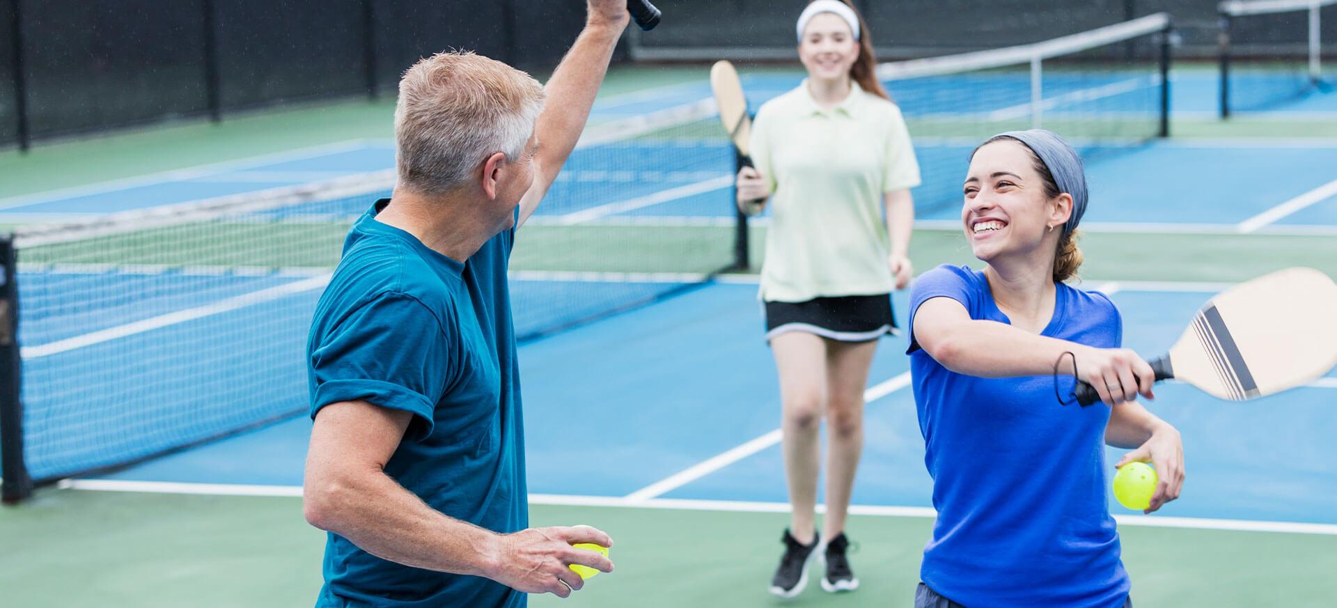 3 Personen spielen Squash