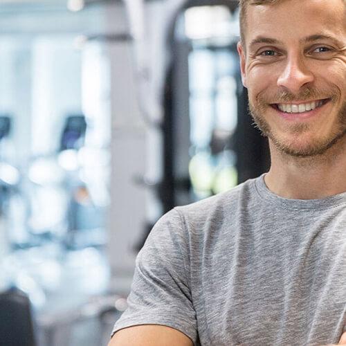 Lächelnder, junger Mann im Fitnessstudio